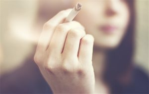 Woman hands holding cigarette outdoor.